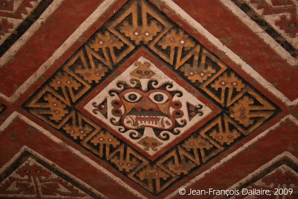 Une tête anthropomorphe d'origine Moche avec des tentacules et entourée de serpents.